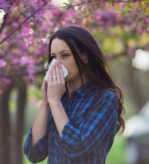 Woman sneezing in tissue outdoors