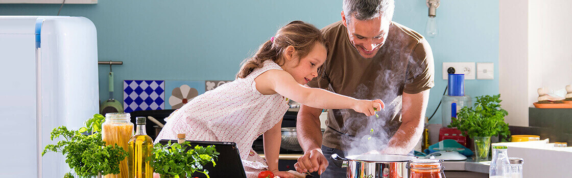 Young girl cooking with dad in kitchen