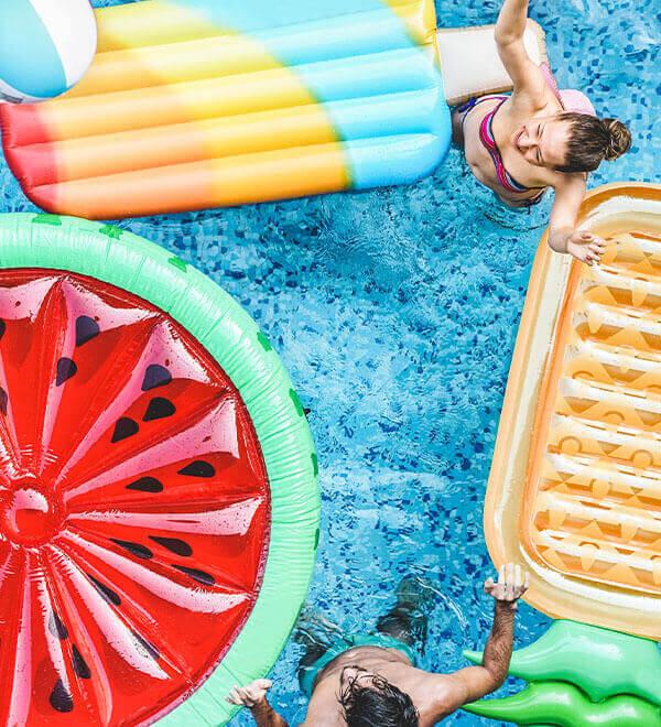 Vrienden spelen met kleurrijke luchtbedden in een zwembad
