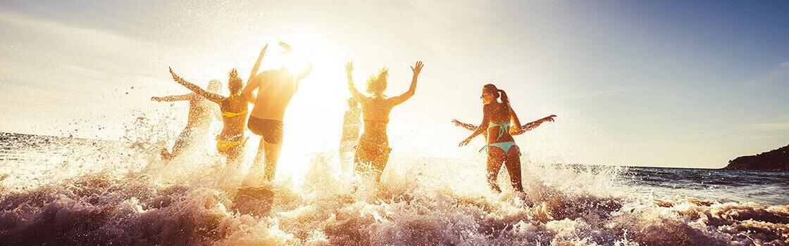Amis qui s'amusent au coucher de soleil, sur la plage, avec vagues.
