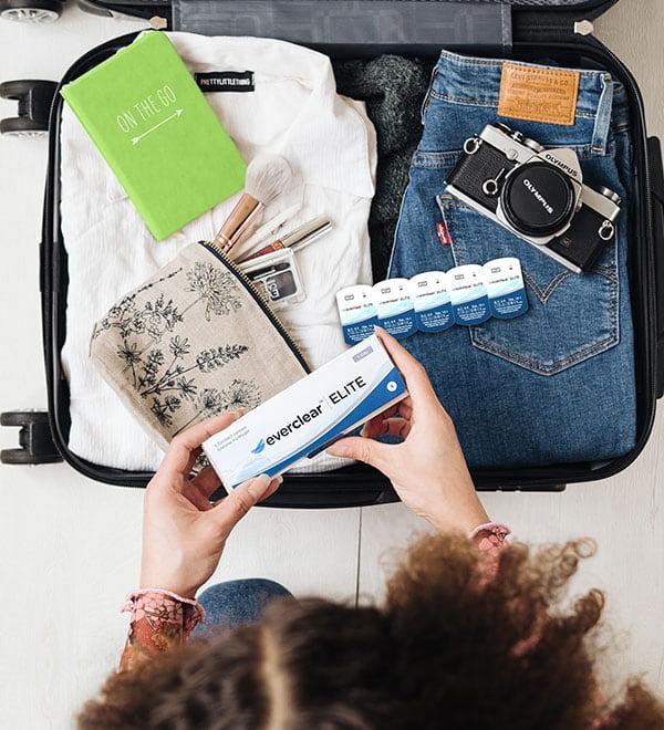 Mujer metiendo una caja de lentillas everclear ELITE en la maleta