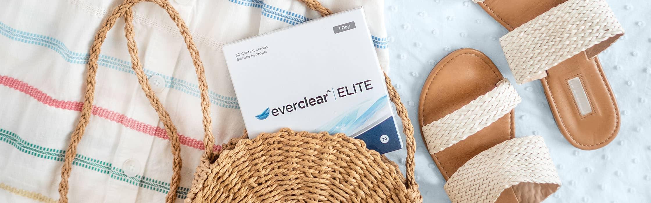 Een doosje everclear ELITE lenzen met een rieten tas en sandalen