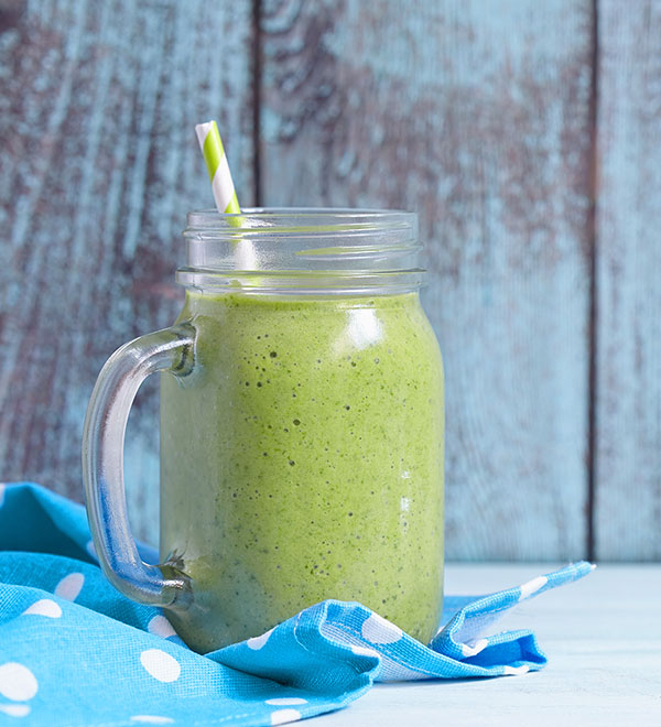 Green smoothie in glass with straw