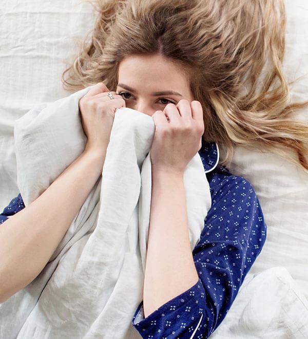 Een vrouw ligt op haar rug in bed met een opgetrokken dekbed