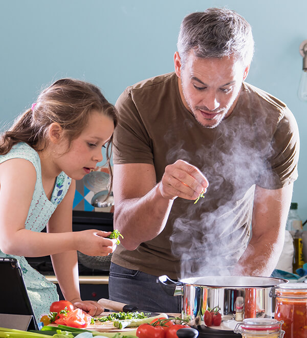 Man and kid cook together in front of a steamy pot