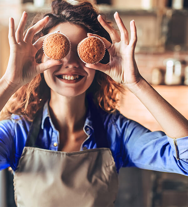 Girl with muffins in front of her eyes