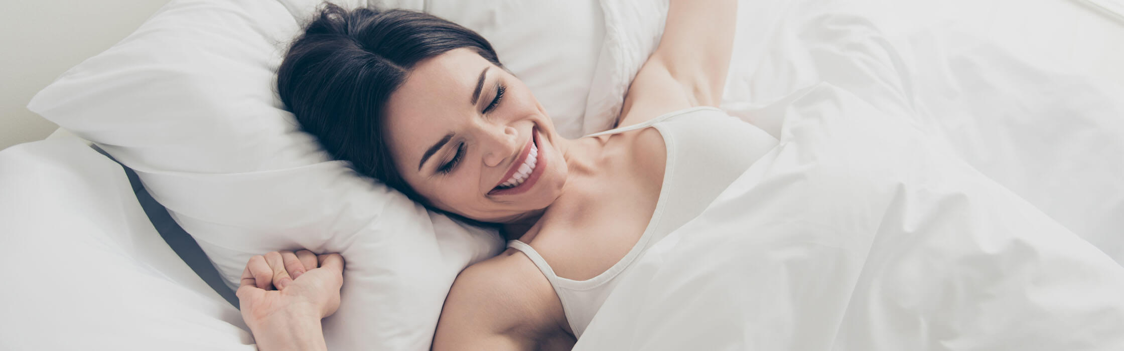 A woman waking up smiling in bed