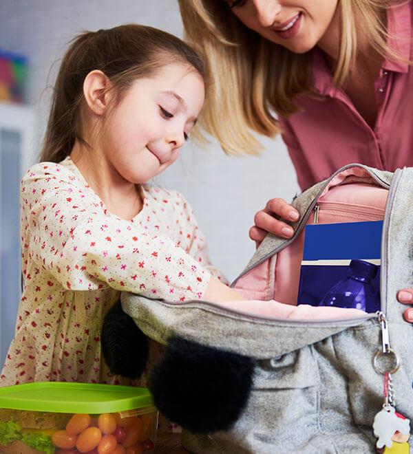 Mother helping daughter pack her school bag