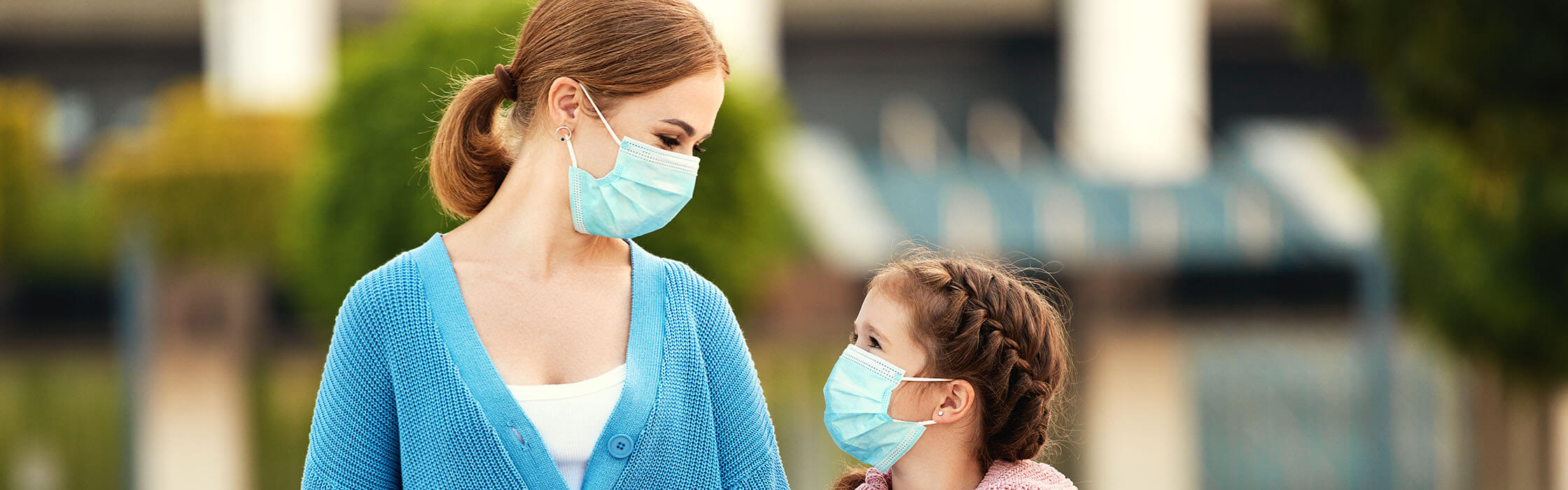 Mother walking daughter to school while wearing face masks
