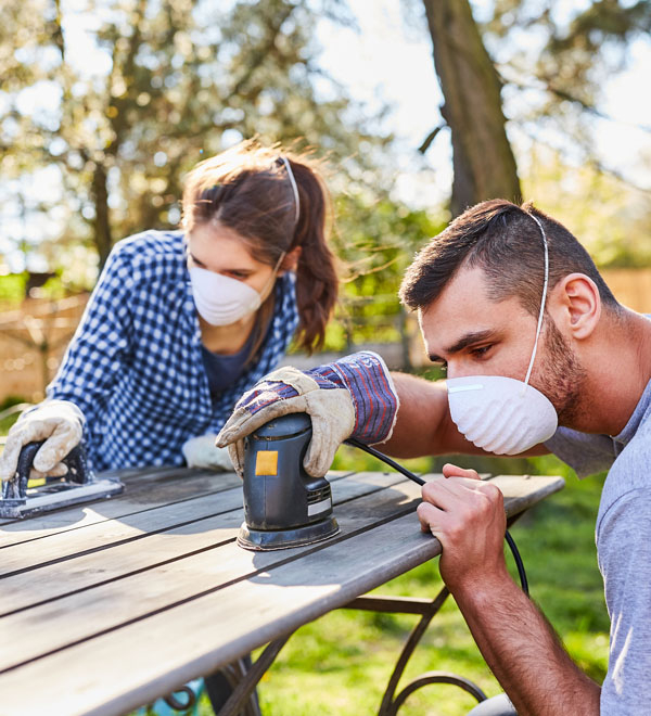 Couple portant des masques et ponçant du bois à l'extérieur