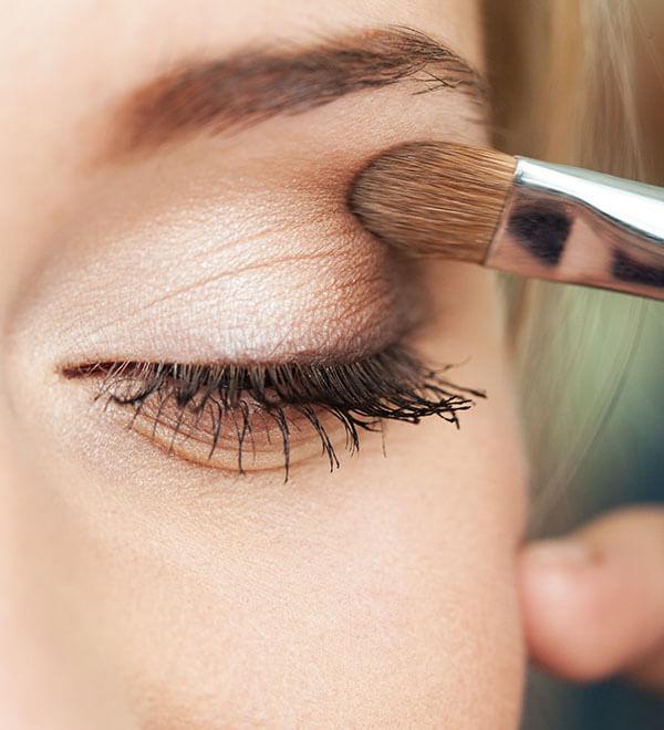 A woman putting on eye shadow