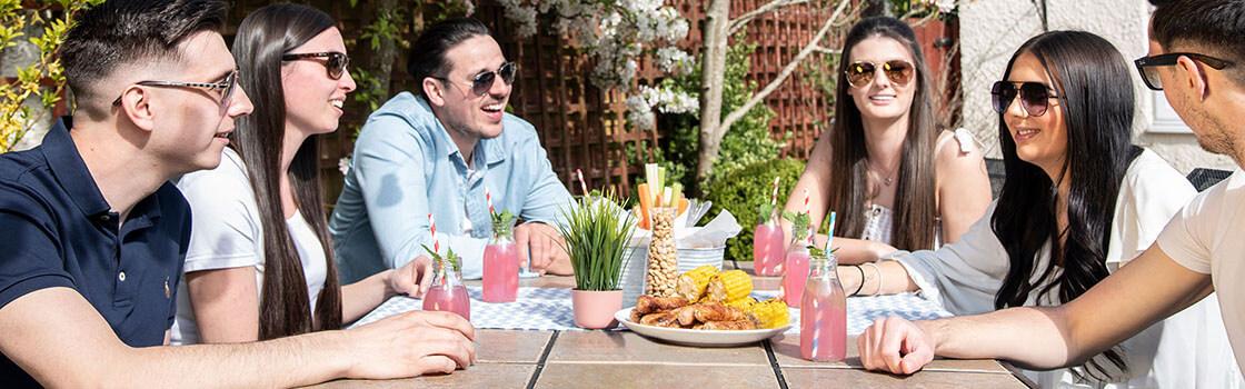 Een groep vrienden buiten in de zon aan tafel