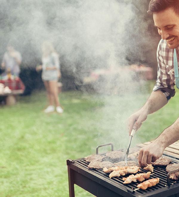 Een man legt vlees op de barbecue