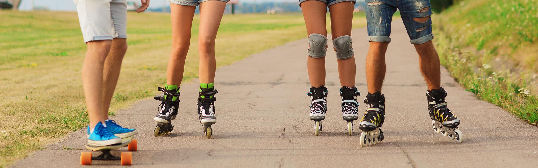 Cuatro pares de piernas con patines y monopatín
