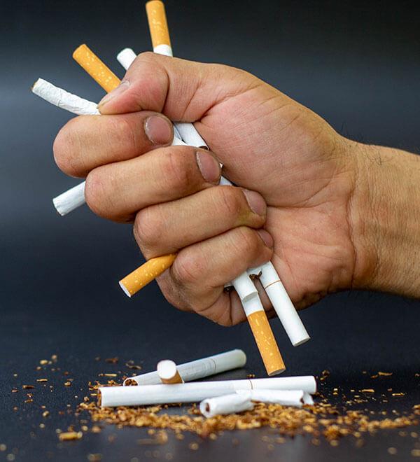 Mains d'une personne écrasant des cigarettes