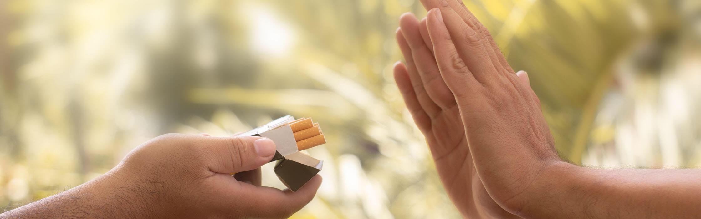 Mains d'une personne refusant un paquet de cigarettes tendu
