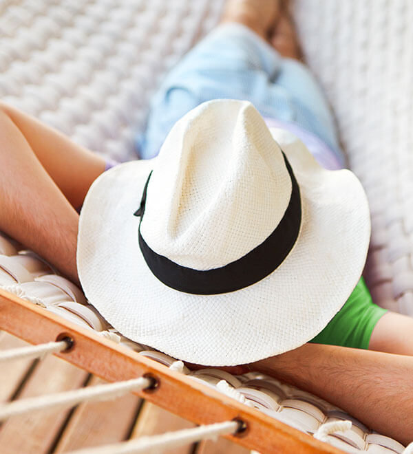 A man wearing a hat, relaxing on a hammock