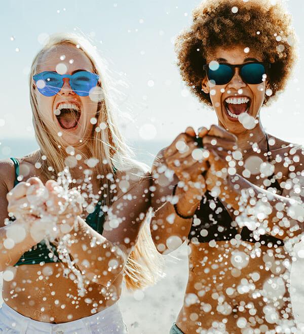Twee vrouwen met zonnebril op staan in de zee