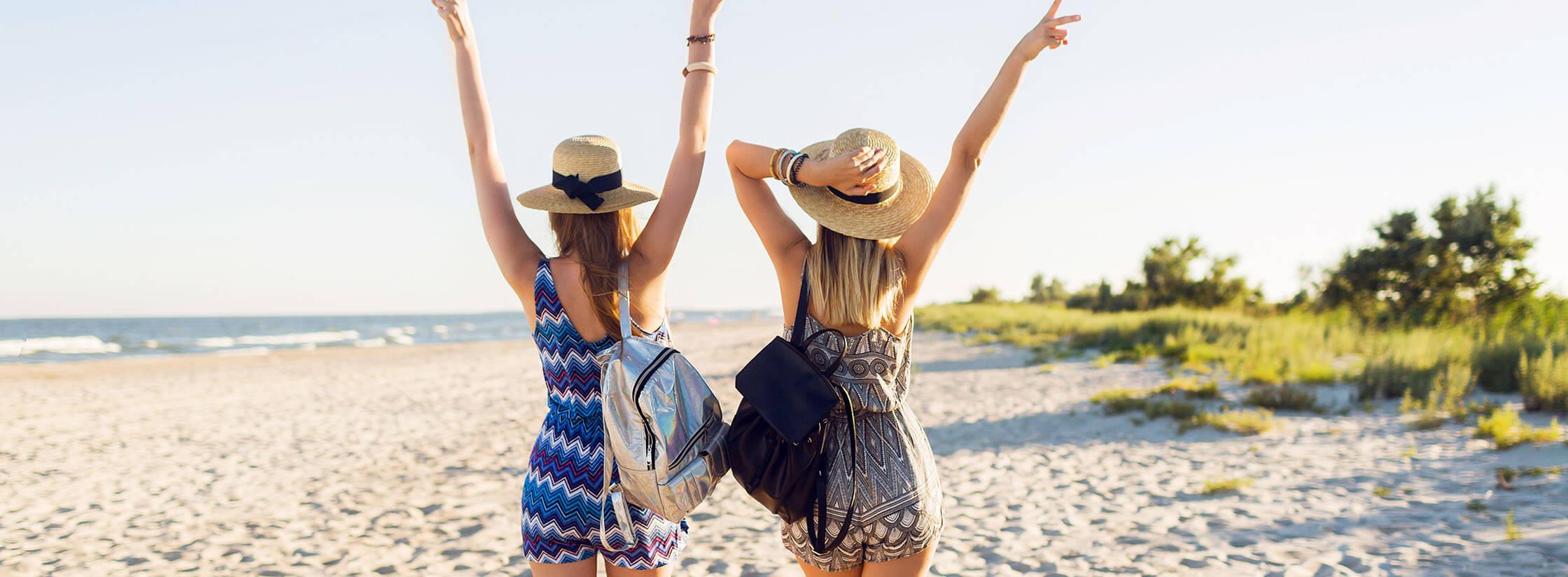 Twee vrouwen met een zomerhoed op lopen op een strand