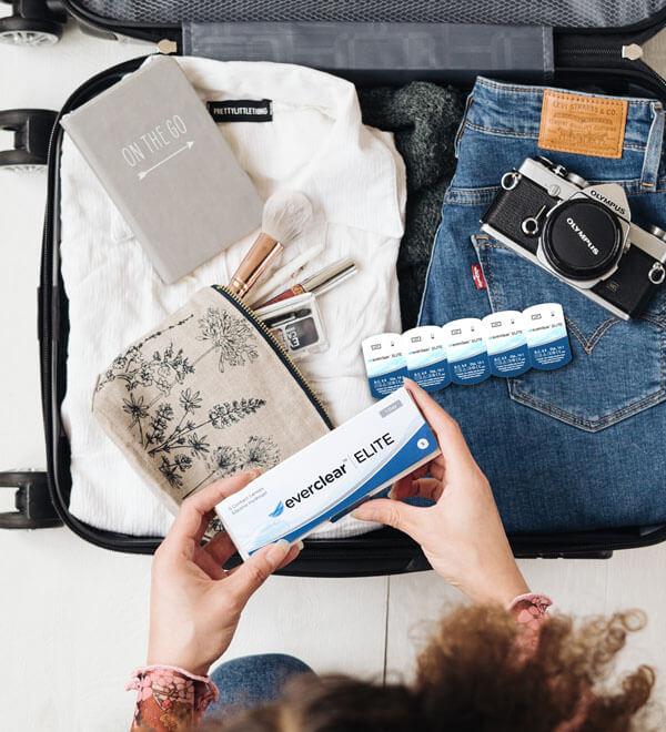 Femme plaçant une boîte de lentilles everclear ELITE dans sa valise de vacances