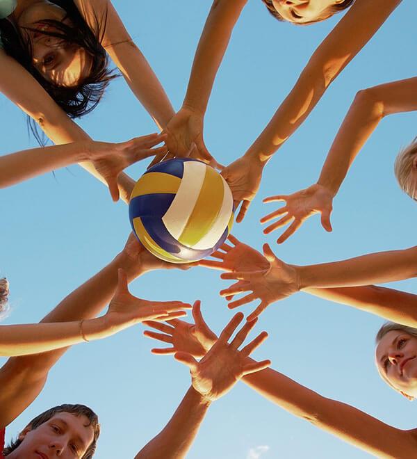 Groupe d'amis tendant les bras pour attraper un ballon