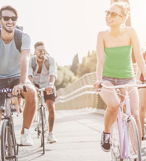 Vier vrienden fietsen op een brug in de zon