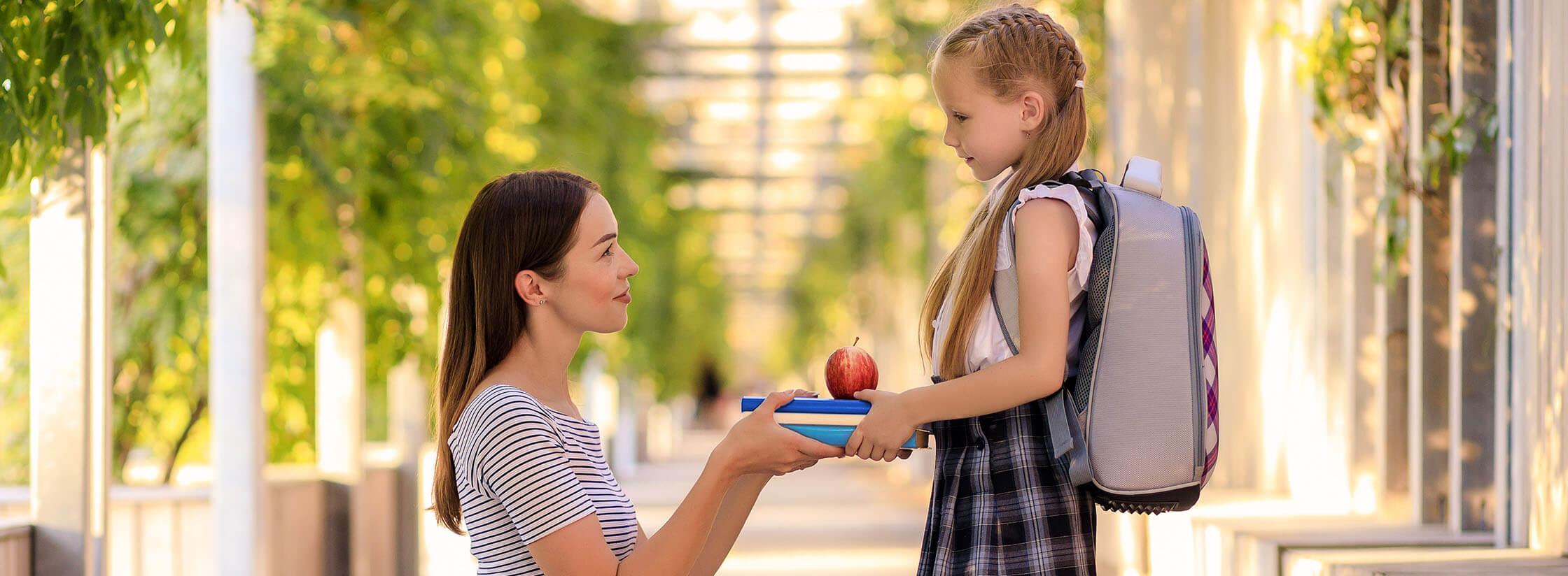 Mère donnant des livres et une pomme à sa fille