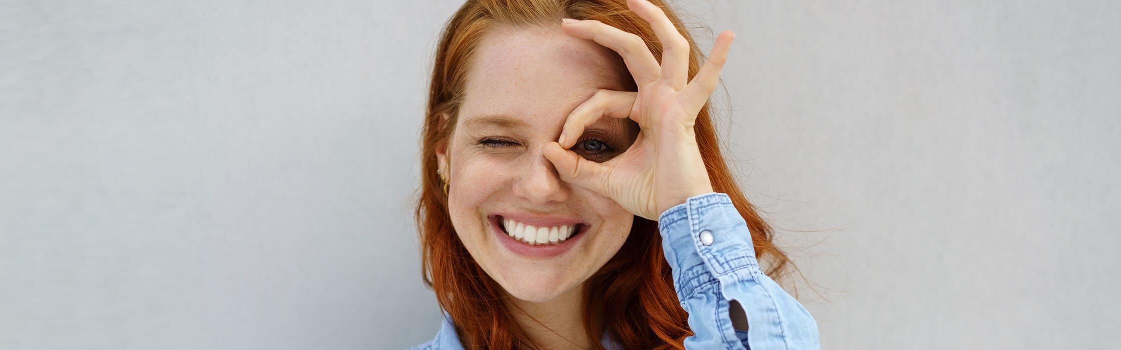 Een lachende vrouw kijkt door haar hand voor haar ogen