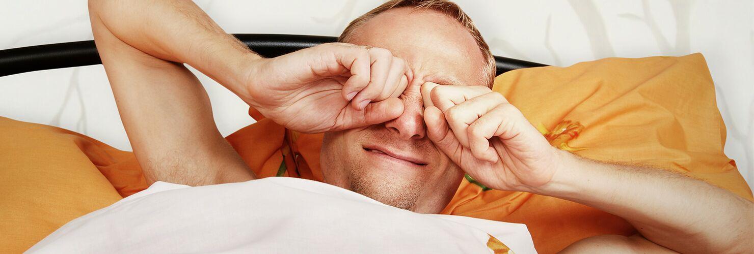 Ragazzo si stropiccia gli occhi nel letto