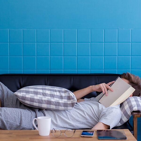 Ragazzo addormentato sul divano dopo aver letto un libro