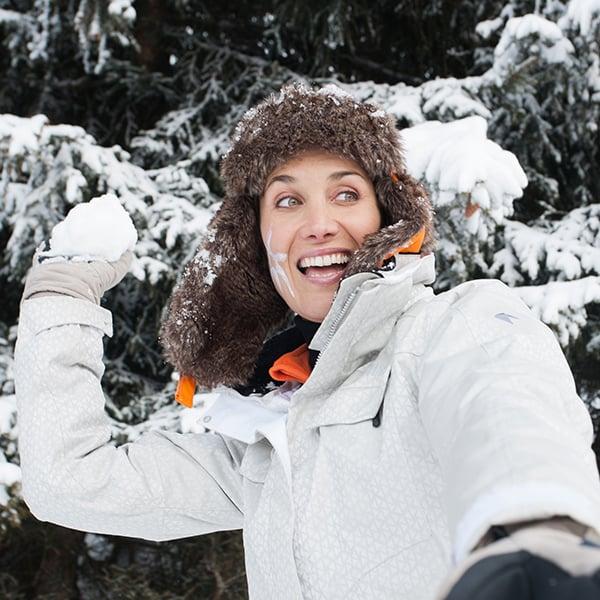 Donna che gioca a palle di neve in inverno
