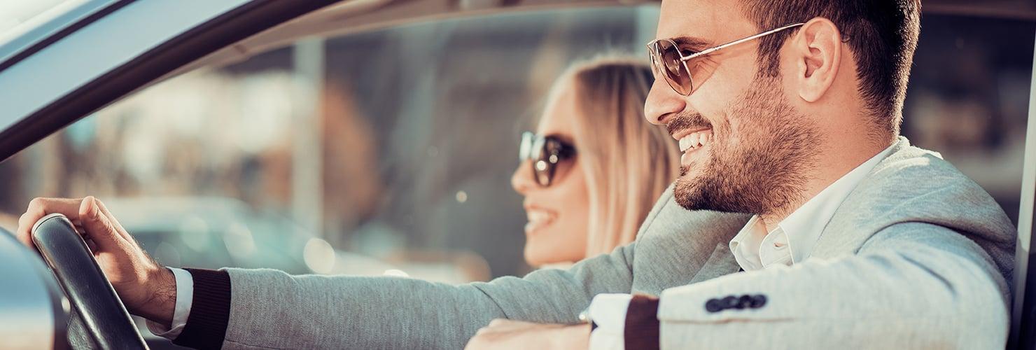 Hombre y mujer conduciendo con gafas de sol