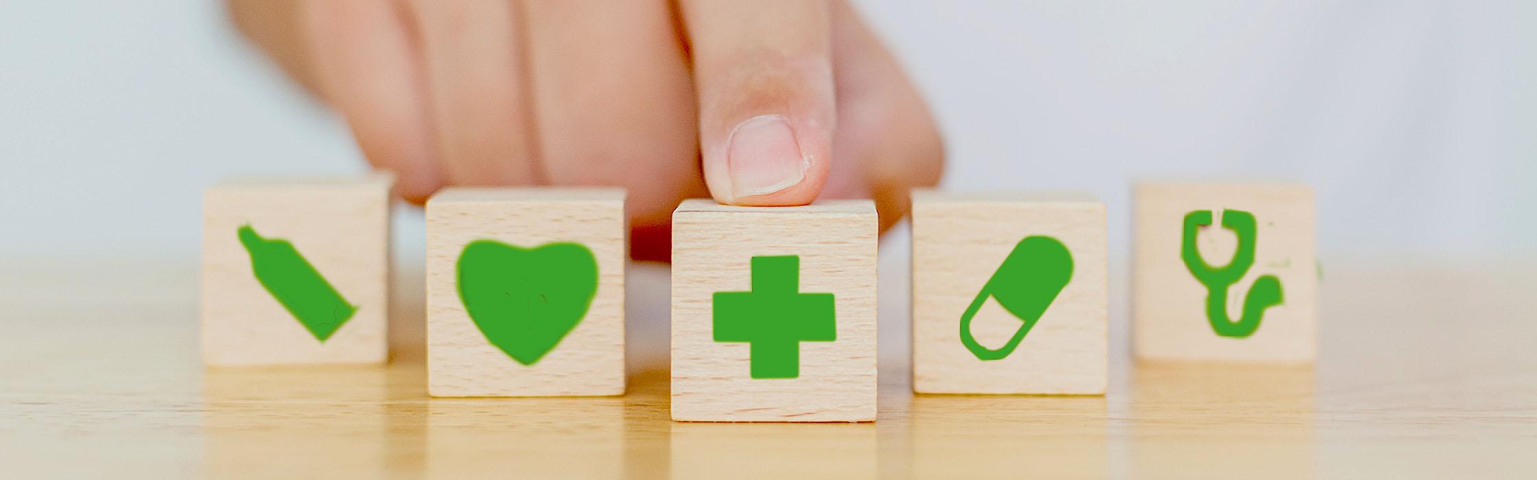 Doigt sur un cube avec une croix verte