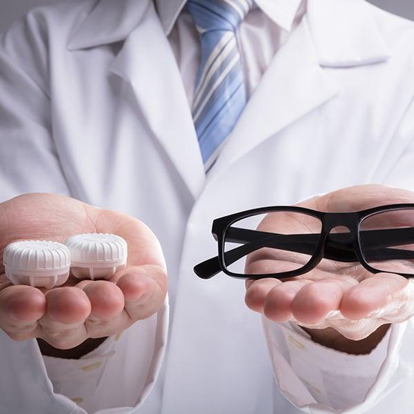 Lemand houdt een bril vast en een contactlenzendoosje