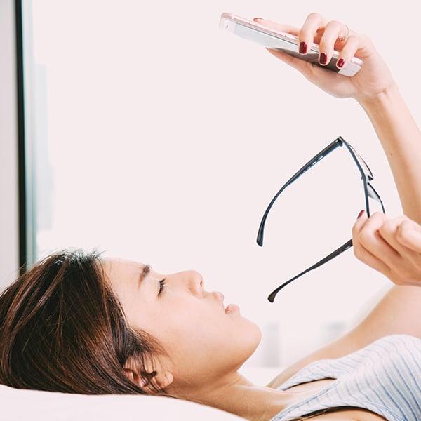 Een vrouw neemt haar bril af terwijl ze een boek leest