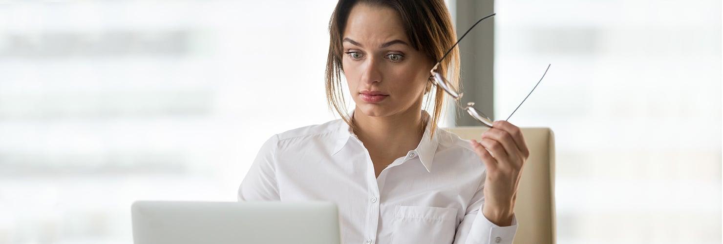 Een man neemt zijn bril af achter de computer.