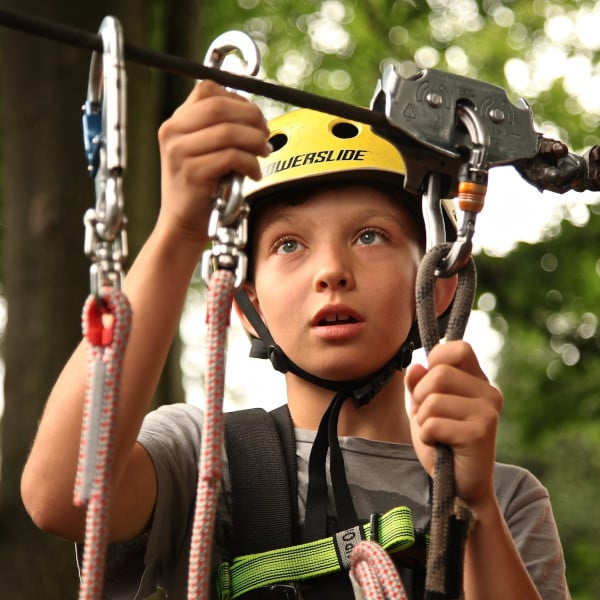 Boy riding zip wire wearing contact lenses