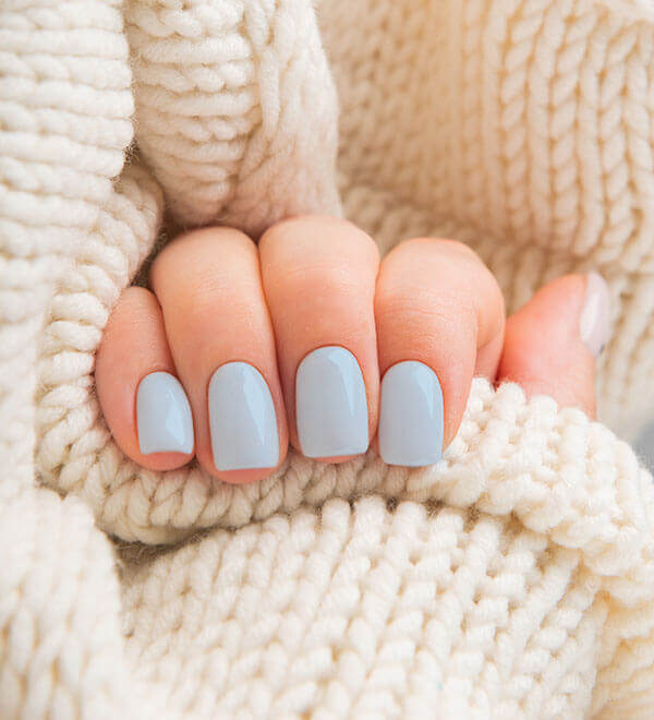 A hand with painted nails holding a knitted jumper