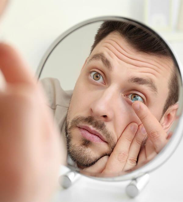 Man kijkt in spiegel en doet contactlens in