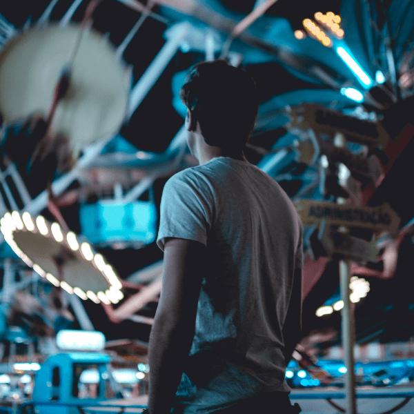 Chico en un parque de atracciones por la noche
