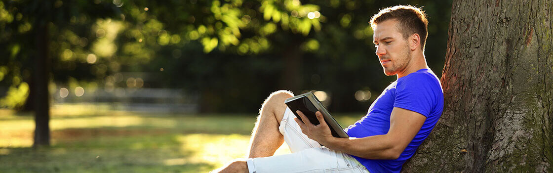 Man reading off ipad outside in the garden