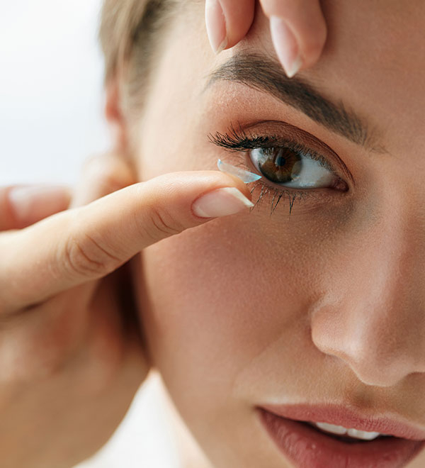 Woman inserting a contact lens into eye