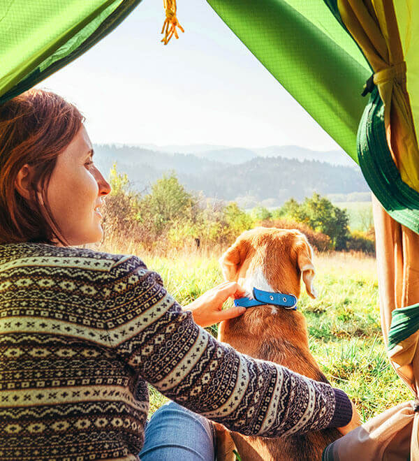 Woman with her dog inside a tent