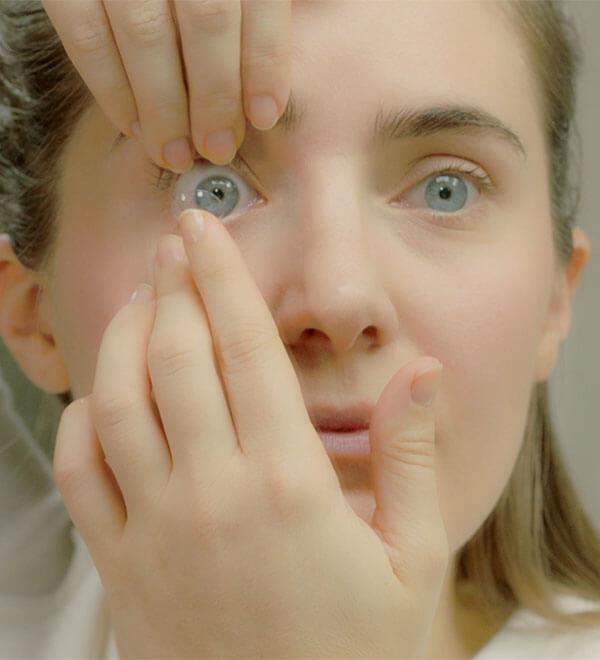 Vrouw doet een lens in haar oog