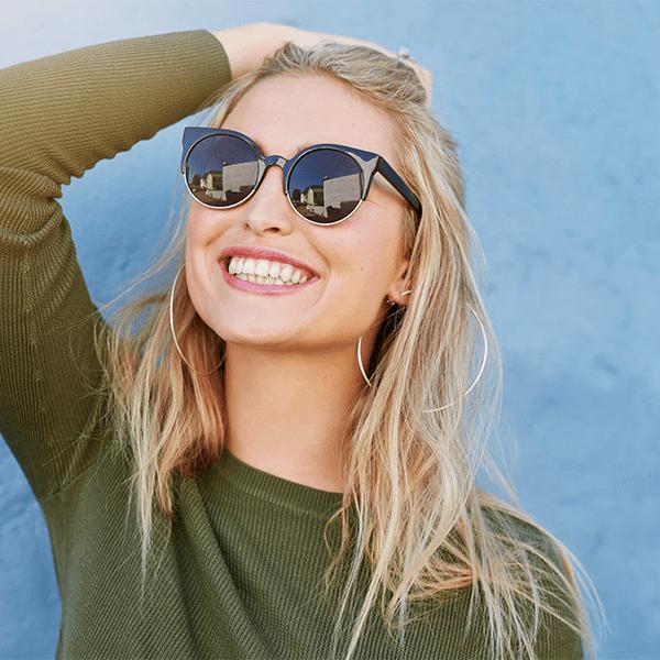 Femme, sourire, porter, lunettes de soleil