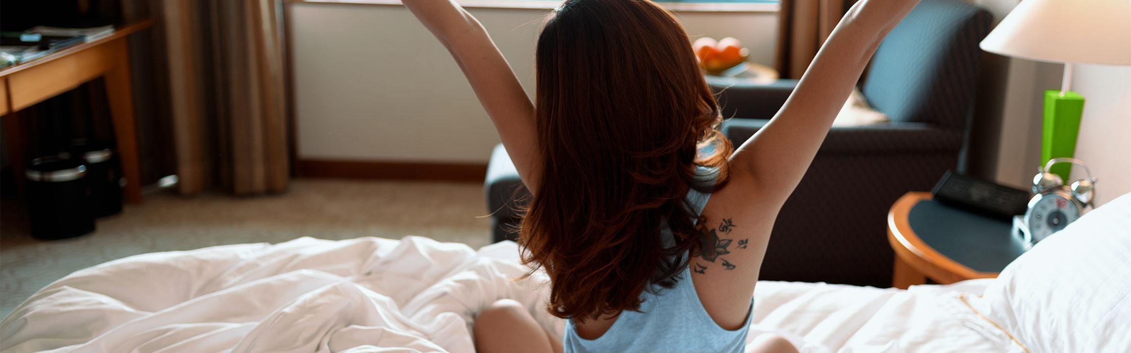 Jeune femme s'étirant au lever