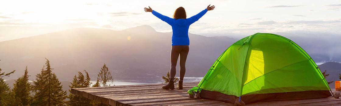 Femme qui s'étend à l'extérieur de la tente sur la montagne
