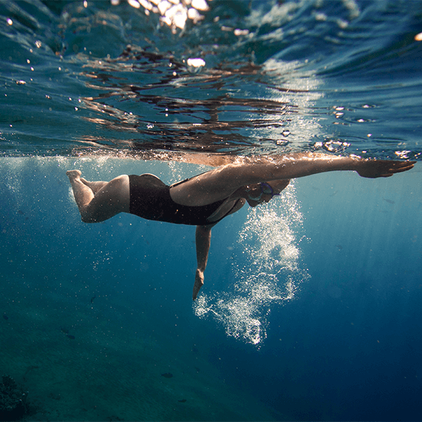 Woman swimming in ocean with goggles