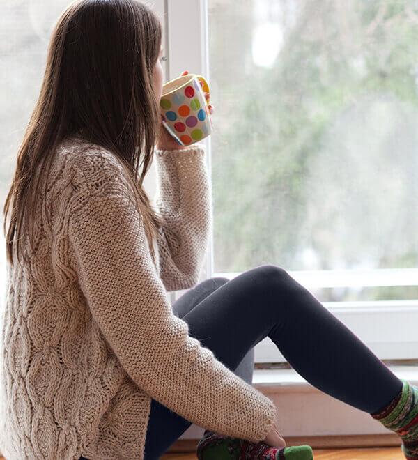 Vrouw kijkt uit het raam met een beker in haar hand