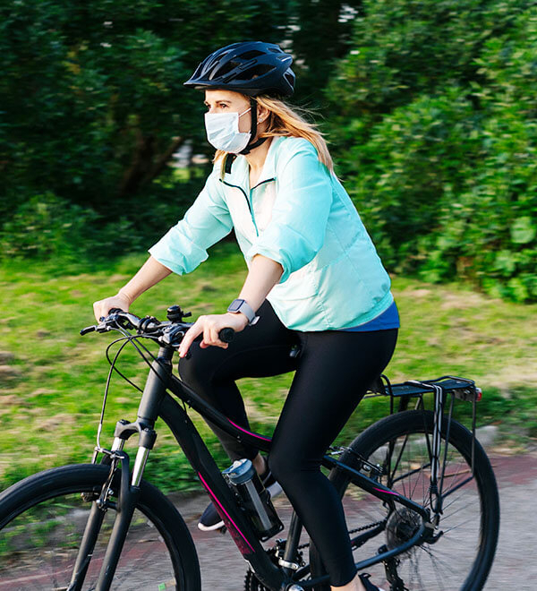 Woman with mask cycling on road